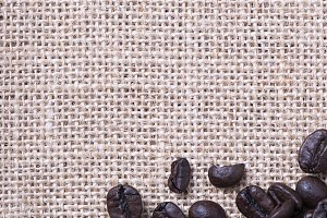 From above shot of coffee beans on tablecloth on wooden table. Vertical shot.