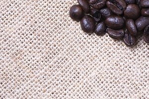 From above shot of coffee beans on tablecloth on wooden table. Vertical shot. Texture.
