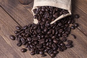 Coffee beans in textile pouch. Vertical indoor shot