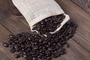 From above shot of coffee beans in textile pouch on wooden table. Horizontal indoor shot
