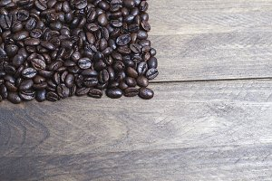 Handful of coffee beans on wooden table