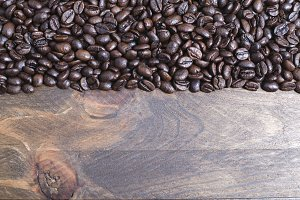 From above shot of handful of coffee beans on wooden table. Horizontal close up shot.