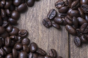 Handful of coffee beans on wooden table. Drink.