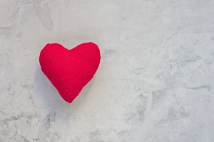 Handmade textile red heart on gray concrete background