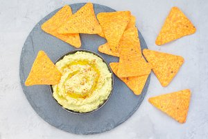 Healthy avocado hummus sprinkled with olive oil, paprika and sesame, served with nachos, horizontal, top view