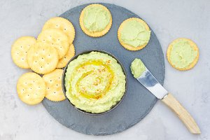 Healthy avocado hummus sprinkled with olive oil, paprika and sesame, served with crackers, horizontal, top view