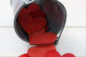 Metal bucket pouring red hearts