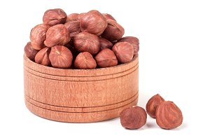 peeled hazelnuts in a wooden bowl isolated on white background