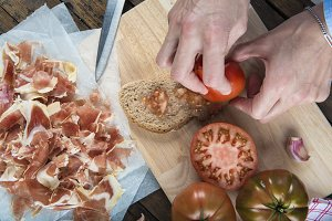 Chef rubbing tomato on a slice of bread