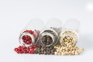 Red, black and white pepper in glass jars