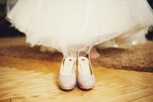 Shoes stand before a bride's legs
