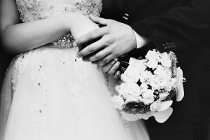 Groom holds bride's hands carefully