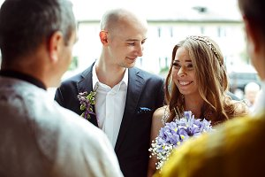 Groom looks at a smiling bride