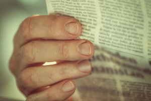Hand holding newspaper