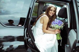 Pretty bride smiles sitting in a car