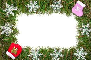 Christmas frame made of fir branches decorated with snowflakes mitten and sock isolated on white background