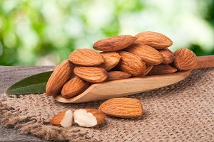heap of peeled almonds with leaf in a wooden scoop on table blurred garden background