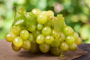 bunch of ripe green grapes on a wooden table with blurred background