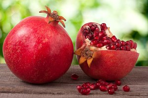 whole pomegranate and  half on the old wooden board with blurred garden background