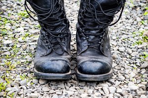 Pair of an old army boots on stones surface, shallow depth of field