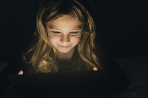Blondie girl playing on a Tablet.