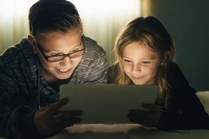 Two kids playing on a Tablet.