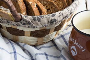 wicker basket with bread,cup of milk