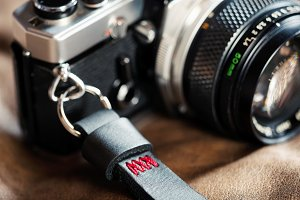 Vintage film camera with leather wrist strap, shallow depth of field