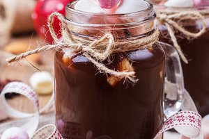 Hot chocolate with marshmallows and spices on christmas table
