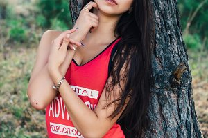 Young beautiful brunette model posing in the sports image of the park against the backdrop  trees