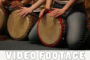 Girls playing on ethnic drums djembe