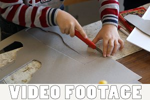 The boy carves model airplane