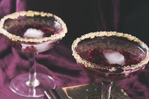 Two alcohol cocktails with berries on purple. Square toned