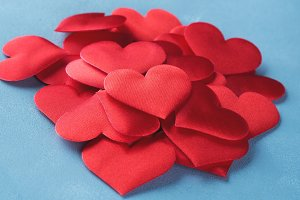 Red hearts on textured background. Vertical card