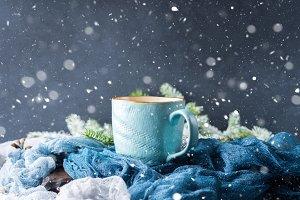 Mug of coffee and milk on dark snow fall background