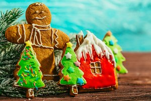 painted gingerbread house, Christmas tree and the man on a blue background