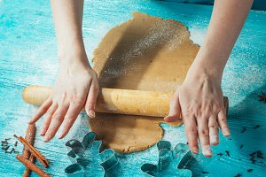 girl rolls the dough on blue wooden table