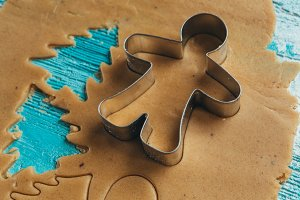 metal molds on dough men tree a blue wooden background