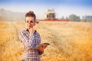 Nice farmer wooman in glasses with hair tied in a ponytail standing with tablet and thinking in wheat field