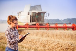 Agronomist girl in glasses keeps a crop accounting in the folder in wheat field