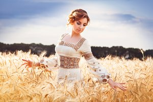 Pretty woman dressed in embroidered clothes in wheat field