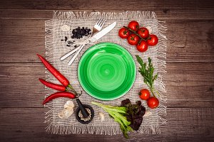Fresh tomatoes, chili pepper and other spices and herbs around modern green plate in the center of wooden table and cloth napkin. Top view. Blank place for your text. Horizontal.