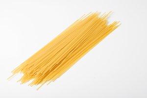 Dried spaghetti on white table