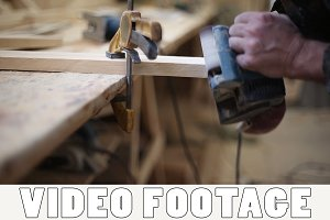 A carpenter polishes a piece of wood