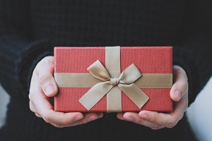 woman hands holding red gift box