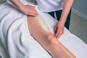 Beautician applying clay treatment in woman legs on spa