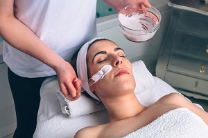 Woman receiving facial mask from beautician in spa