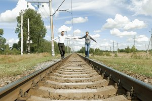 Man and woman holding hands walking along railway