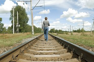 Woman walks along railway tracks in countryside