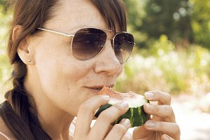 Smiley woman eats an watermelon outdoors on summer